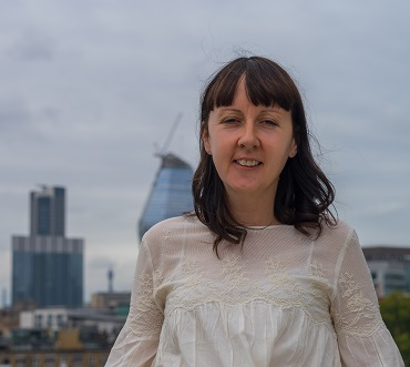 Lady with dark brown hair with london skyline background