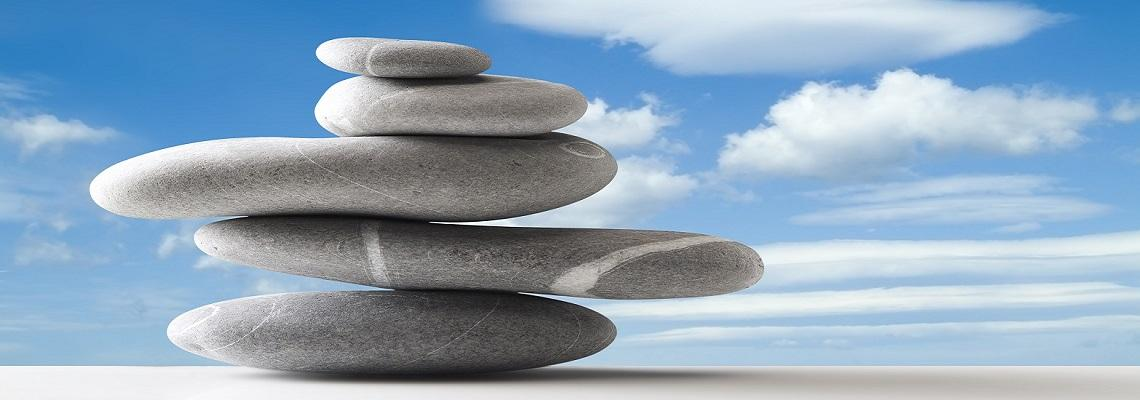 Zen stones stacked with blue sky and cloud background