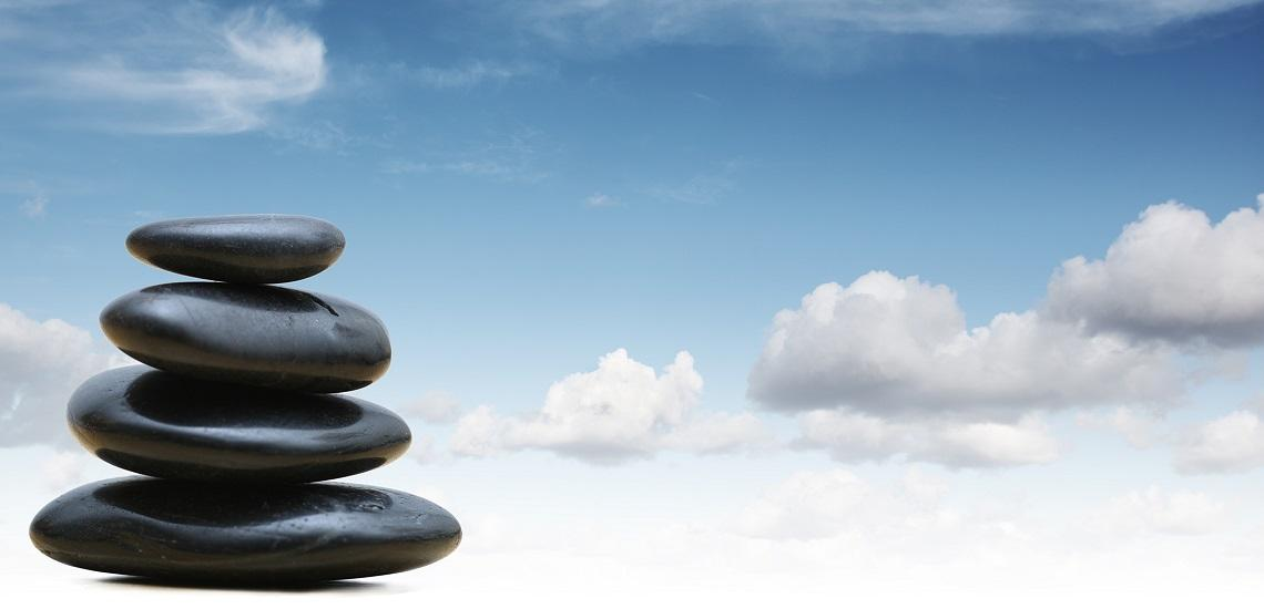 Black zen stones with blue sky and cloud background
