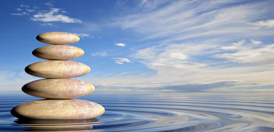 Zen stones with a blue sky background and clouds