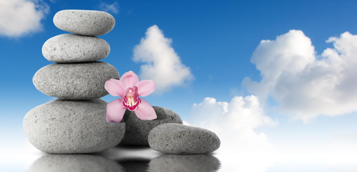 Zen stones with flower on rippling water with blue sky and clouds