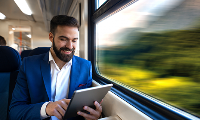 Man working on his tablet on a train