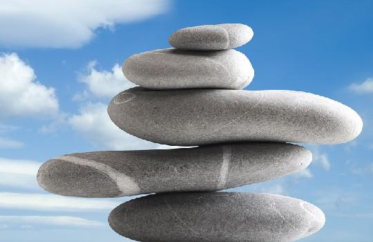 Stacked zen stones with clouds and blue sky background