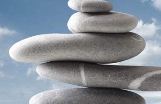 Close up of stacked zen stones with clouds and blue sky background
